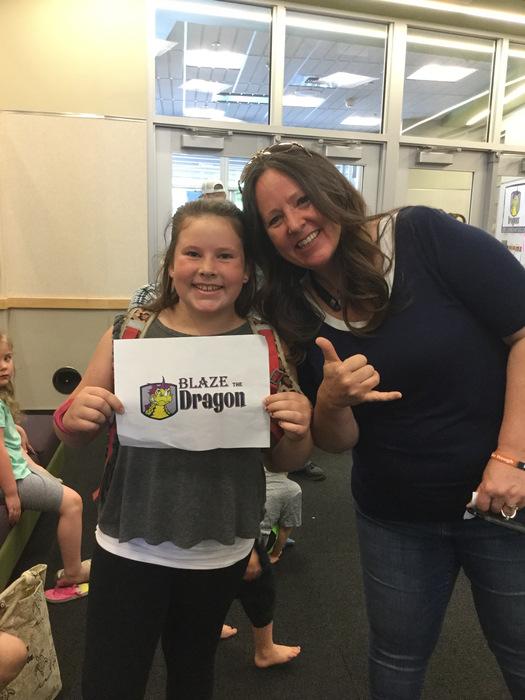 PTA President Kerri Boggs and her daughter, Samantha, pose with the reveal slip of the Davis Dragon name after our last all school assembly.